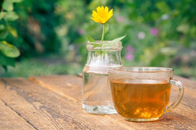 Tasse de thé vert et fleur de calendula avec une tige dans un flacon en verre sur des planches en bois.