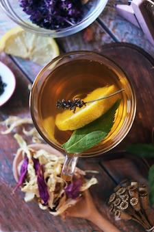 Une tasse de thé vert avec des fleurs d'herbes utiles et des pétales secs de citron de plantes utiles