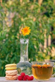 Tasse de thé vert, gâteaux de macarons de différentes couleurs, framboises fraîches et fleur de calendula.