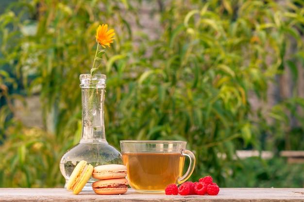 Tasse de thé vert, macarons délicieux, framboises fraîches et fleur de calendula dans un flacon en verre