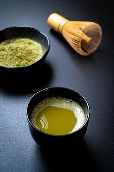 Tasse de thé vert matcha chaud avec poudre de thé vert et fouet
