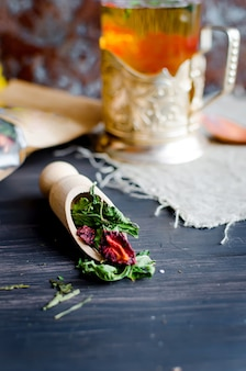Tasse de thé vert à la menthe, tranche de citron, rouleau de fruits secs et thé feuilles de menthe à la fraise