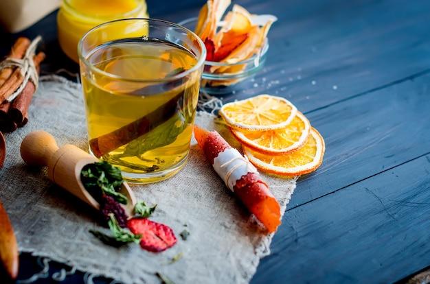 Tasse de thé vert à la menthe, tranche de citron, rouleau de fruits secs et thé à la menthe