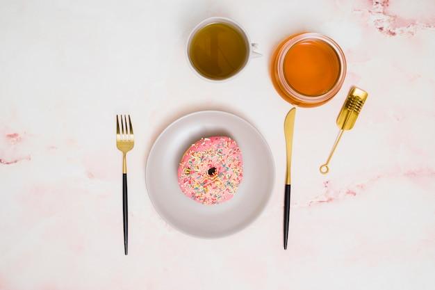 Tasse de thé vert; miel et beignet rose sur une plaque blanche avec une fourchette et un couteau à beurre sur fond blanc