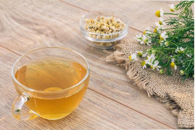 Tasse de thé vert, petit bol en verre avec des fleurs sèches de matricaria chamomilla et des fleurs de camomille blanches sur un sac et un fond en bois.