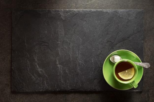 Tasse de thé vert et surface en ardoise