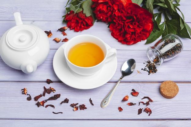 Tasse de thé vert sur la table avec des fleurs de pivoine fraîche