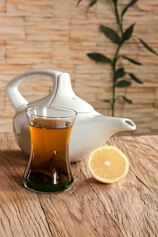 Une tasse de thé vert et une théière sur un mur de fond avec revêtement en pierre
