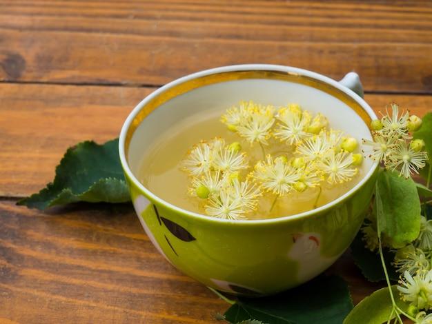Tasse de thé vert et de tilleul sur fond de bois, concept de médecine populaire de fleurs de tilleul utile