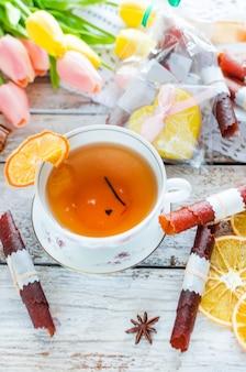 Tasse de thé vert avec tranche de citron, rouleau de cuir aux fruits secs et biscuits au gingembre