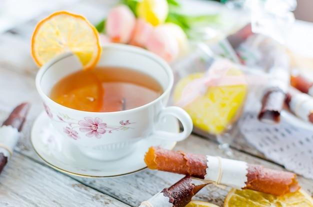 Tasse de thé vert avec tranche de citron, rouleau de cuir de fruits secs et biscuits au gingembre, tulipes