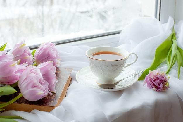 Tasse de thé un vieux livre un bouquet de tulipes sur la fenêtre