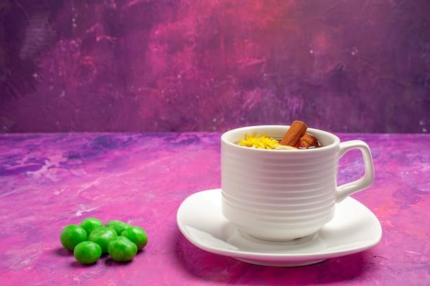 Tasse de thé vue de face avec des bonbons verts sur des bonbons de couleur thé rose