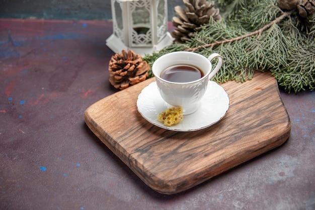 Tasse de thé vue de face avec des cônes sur un espace sombre