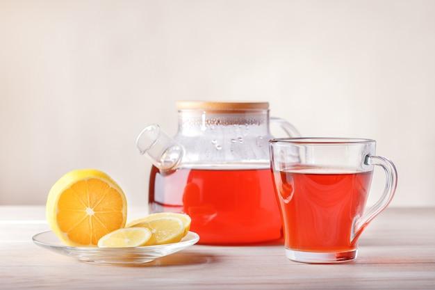 Tasse et théière avec thé, citron sur table. thé aux fruits avec une tranche d'agrumes.