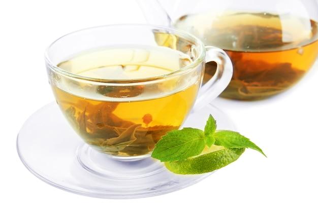 Tasse et théière de thé vert sur blanc