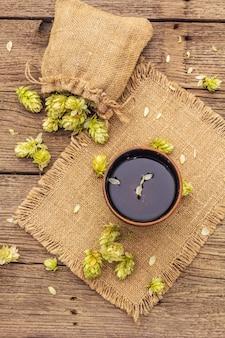 Tasse de tisane apaisante avec du houblon sauvage frais. cônes de houblon en sac sur planches vintage