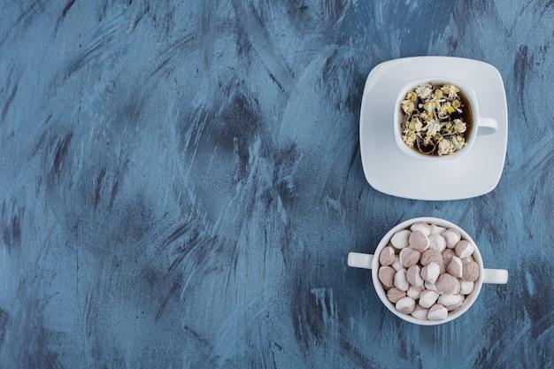 Tasse de tisane avec bol de bonbons bruns sur bleu.