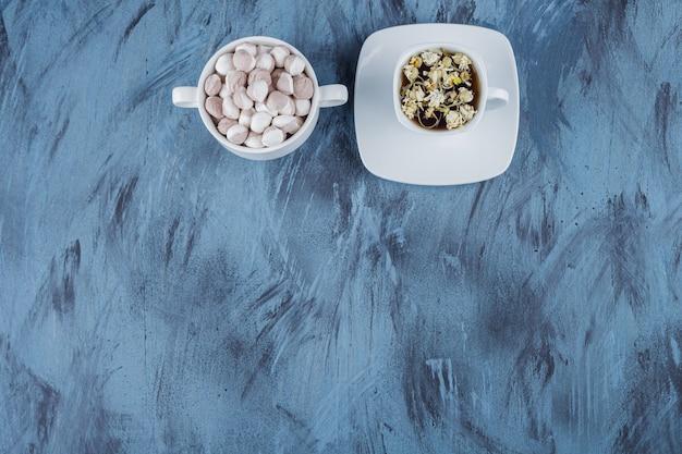 Tasse de tisane avec bol de bonbons bruns sur fond bleu.