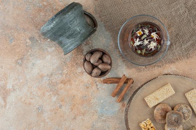 Une tasse de tisane avec une bouilloire ancienne et des brittles aux arachides