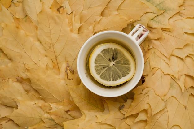 Une tasse de tisane chaude au citron sur les feuilles d'automne jaunes.