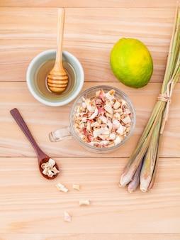 Tasse de tisane avec citronnelle séchée, miel et citron sur fond de bois.