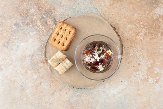 Une tasse de tisane avec des gaufres sur planche de bois
