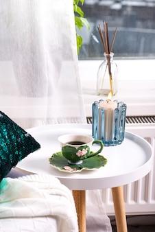 Une tasse de tisane sur une table, une couverture de laine tricotée sur une chaise et une bougie sur la fenêtre. intérieur de la chambre