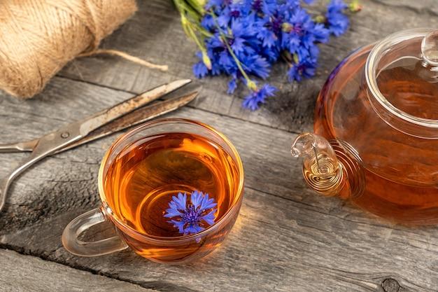 Tasse de tisane, théière et fleurs de bleuets bleus