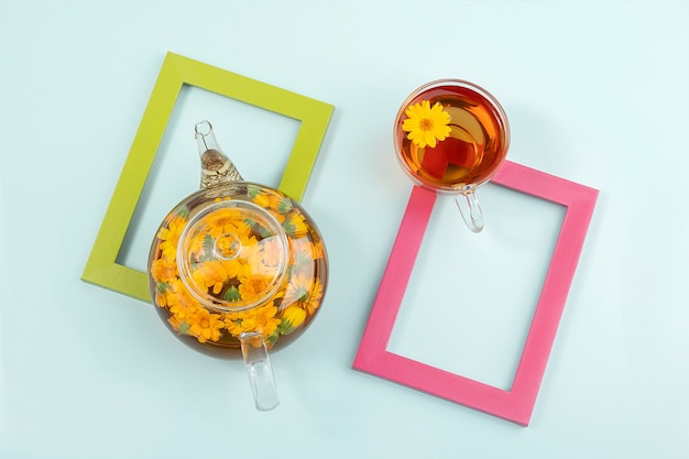 Tasse de tisane et théière transparente avec des fleurs de calendula