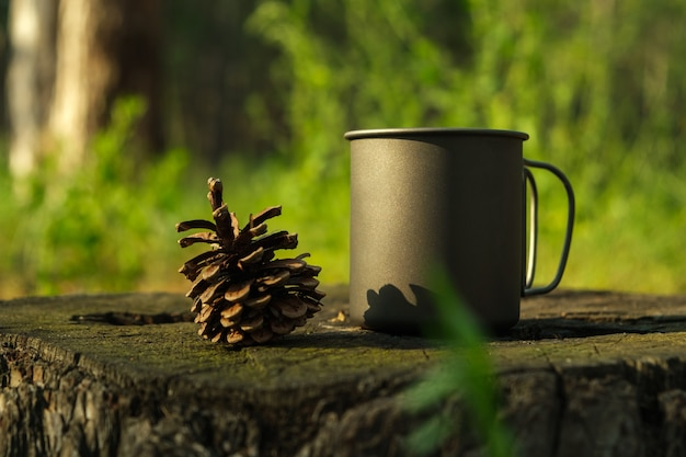 Une tasse en titane et une pomme de pin se tiennent sur une souche dans une forêt