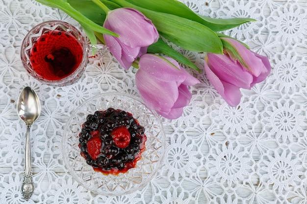 Tasse transparente en cristal de bohême de thé rouge karkadeh avec gâteau aux baies et tulipes sur une belle nappe au crochet