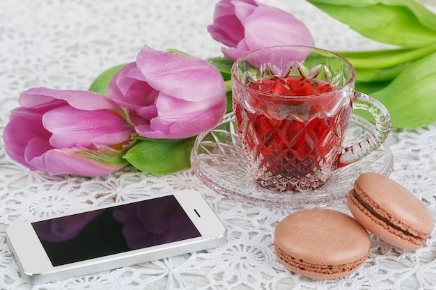 Tasse transparente en cristal de bohème de thé rouge karkadeh avec macarons cookies, smartphone et tulipes perple sur une belle nappe au crochet