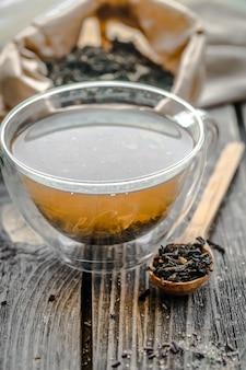 Tasse transparente de thé infusé avec des cuillères en bois adjacentes, du sucre et du thé sur fond de bois
