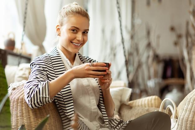 Tasse de transport. dame séduisante avec un large sourire sirotant du thé chaud dans une tasse tout en se relaxant dans le salon