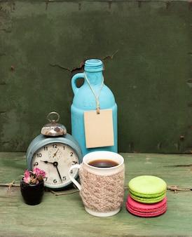 Tasse tricotée, macarons, bouteille bleue et horloge sur vert grunge