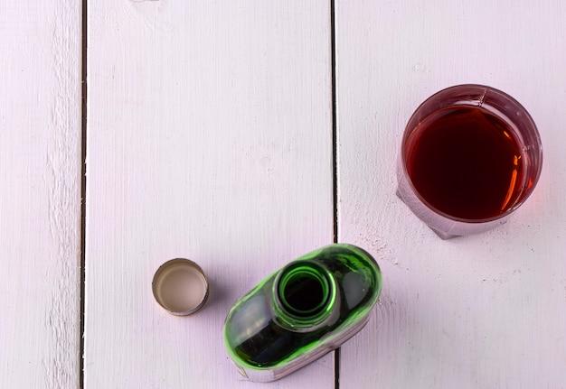 Tasse en verre avec de l'alcool et ouvrez une bouteille de whisky sur une table en bois blanche. vue d'en-haut