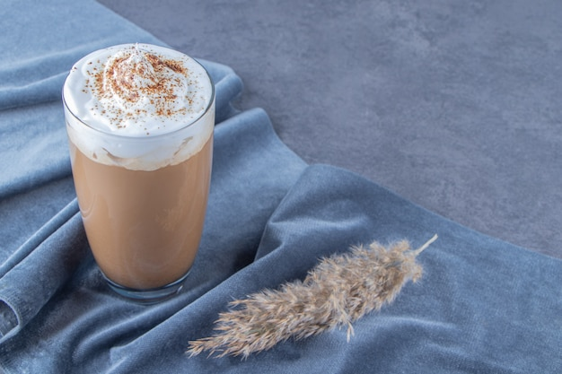 Tasse en verre de café au lait sur un morceau de tissu à côté de l'herbe de la pampa, sur fond bleu.