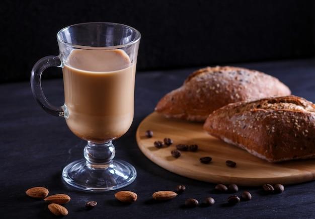 Tasse en verre de café avec de la crème et des petits pains sur fond noir