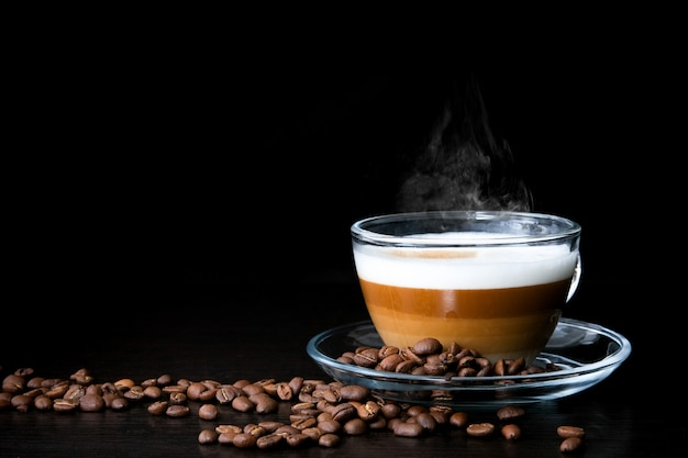Tasse en verre de cappuccino chaud avec des couches de café