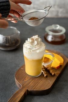 Une tasse de verre de cappuccino épicé à la citrouille sur fond gris