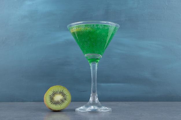 Une tasse en verre à cocktail de jus de kiwi avec une tranche de fruit.
