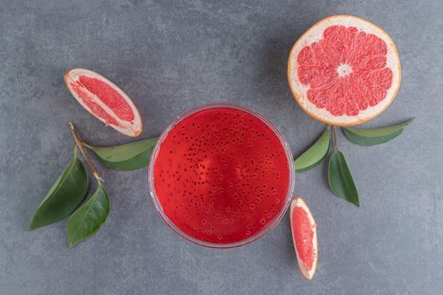 Une tasse en verre avec du jus rouge et des tranches de pamplemousse