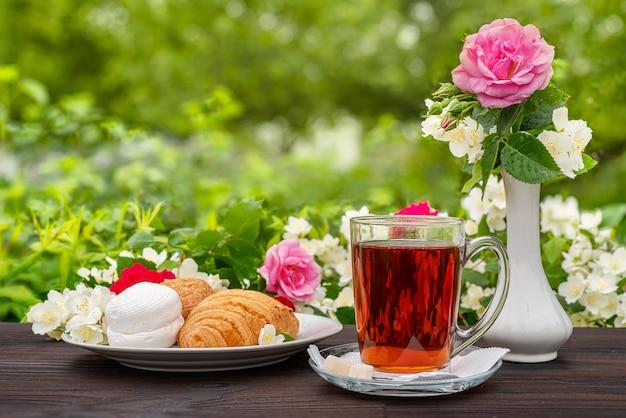 Tasse en verre avec du thé et des morceaux de guimauves de croissants au sucre