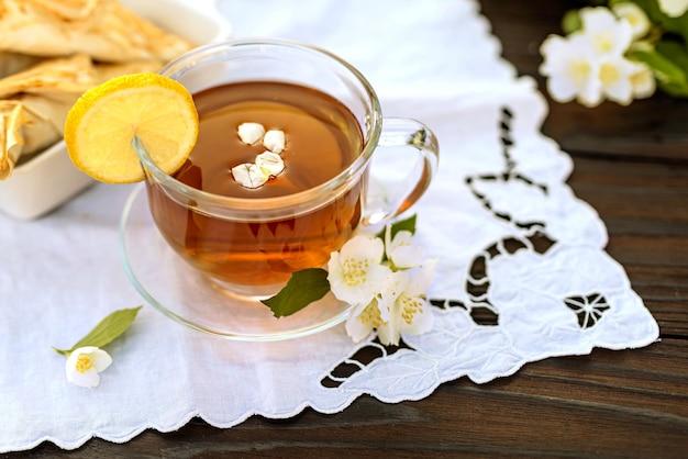 Tasse en verre avec du thé et des pétales de croissants au citron serviette brodée