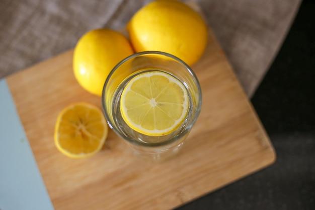 Tasse en verre avec de l'eau et du citron sur planche de bois
