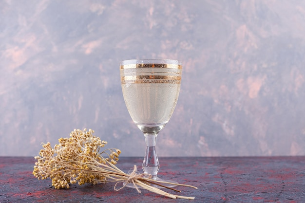 Une tasse en verre d'eau minérale avec fleur séchée placée sur un fond sombre.