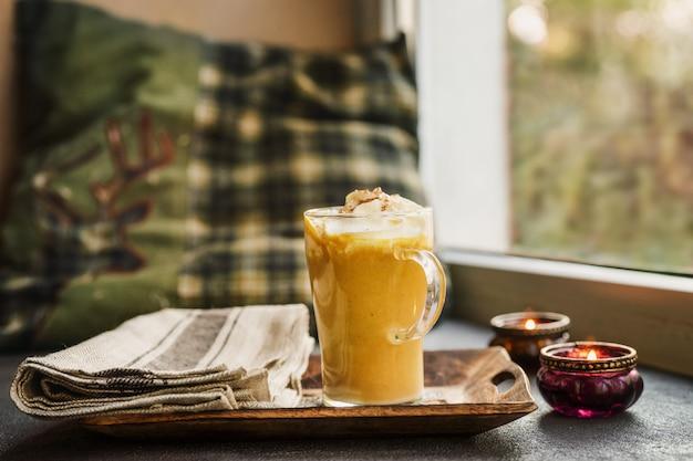 Une tasse de verre d'épice de citrouille au lait à côté d'une fenêtre