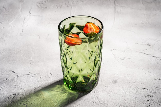 Une tasse en verre géométrique verte avec de l'eau fraîche et des fruits aux fraises