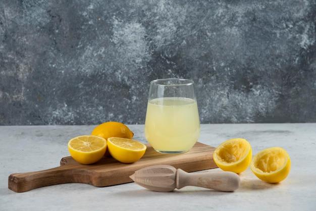 Une tasse en verre de jus de citron frais sur une planche de bois.